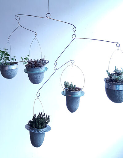 Five paperpulp vessels in frames made from recycled materials and suspended.