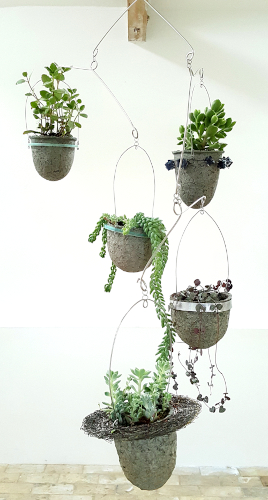 Paperpulp vessels with recycled materials frames and succulents