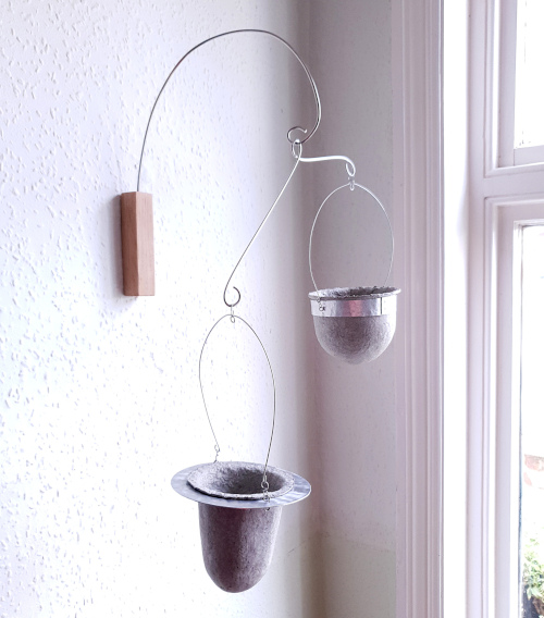 Two suspended vessels held in upcycled aluminium frames from oak bracket