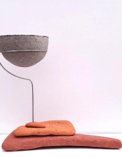 Paperpulp vessel held in stainless steel frame above sea sculpted tiles