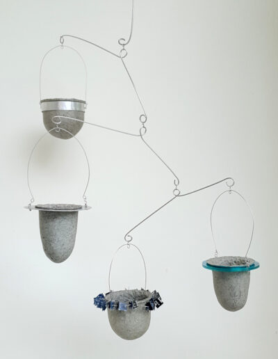 Four paper pulp vessels held in decorative frames suspended in stainless steel mobile
