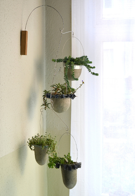 Four paper pulp vessels held in decorative frames suspended from oak wall mount